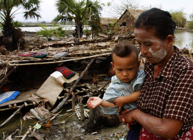 Survivors of Cyclone Nargis walk near a village destroyed by the cyclone in southern Myanmar in May, 2008.