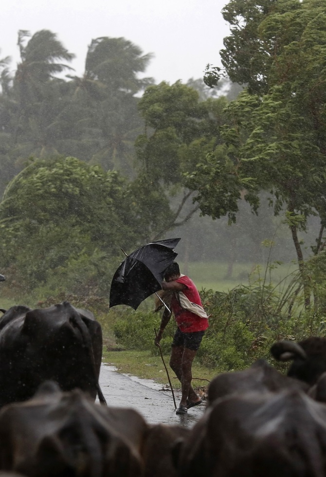 A boy tries to cover himself with an umbrella during heavy rain brought by Cyclone Phailin in Ichapuram town in Srikakulam district