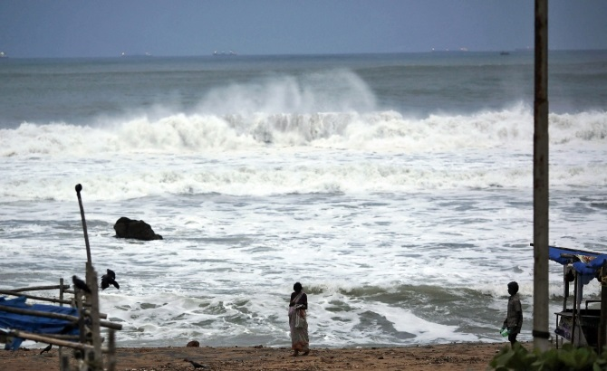 People stand as waves from the Bay of Bengal approach the shore in Visakhapatnam district
