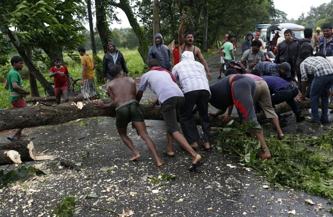 Men try to remove fallen trees from a road due to the rain and wind in Odisha
