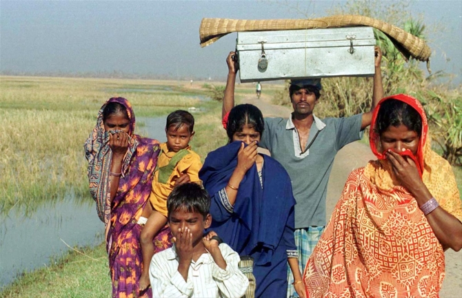 Residents cover their noses to avoid the stench from the badly decomposed bodies and carcasses on the way to safe place in Ersama village after the 1999 cyclone