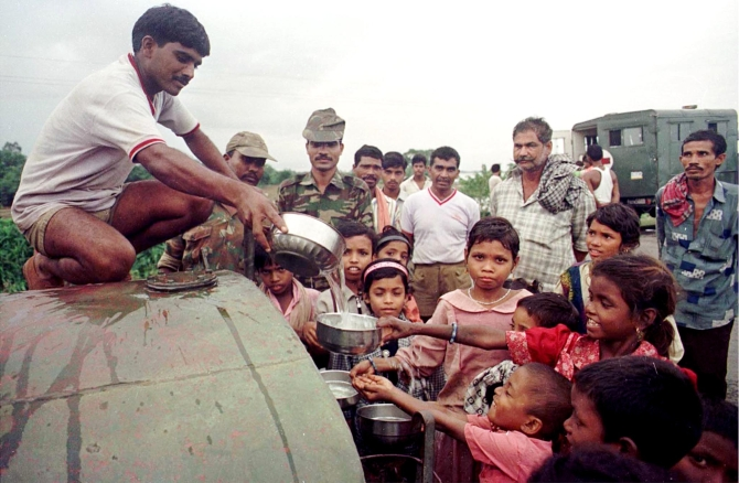 Soilders distribute drinking water at a village hit by the cyclone in 1999