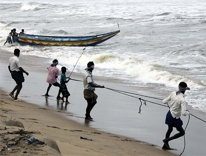 Fishermen pull a boat from the waters of the Bay of Bengal to safer ground at Podampata village in Ganjam district in the eastern Indian state of Odisha