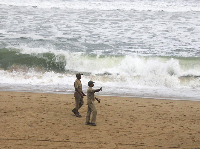-Police direct people to move away as waves from the Bay of Bengal approach the shore at Podampata village in Ganjam district in the eastern Indian state of Odisha