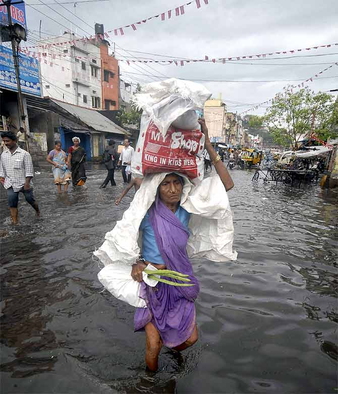A woman carries a bag as she walks through a flooded street after heavy rains