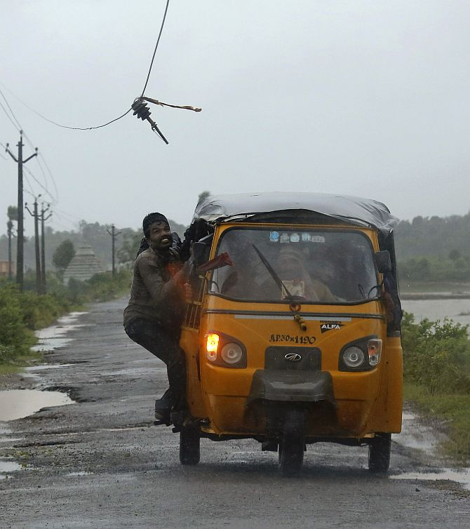 A man tries to avoid a broken electricity cable as he rides on an auto rickshaw in Ichapuram town in Srikakulam district of Andhra Pradesh