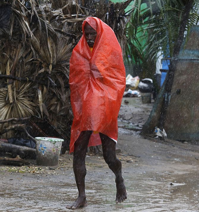 A man covers himself with a plastic sheet during heavy rain brought by Cyclone Phailin as he moves towards a safer place at the village Donkuru in Srikakulam district.