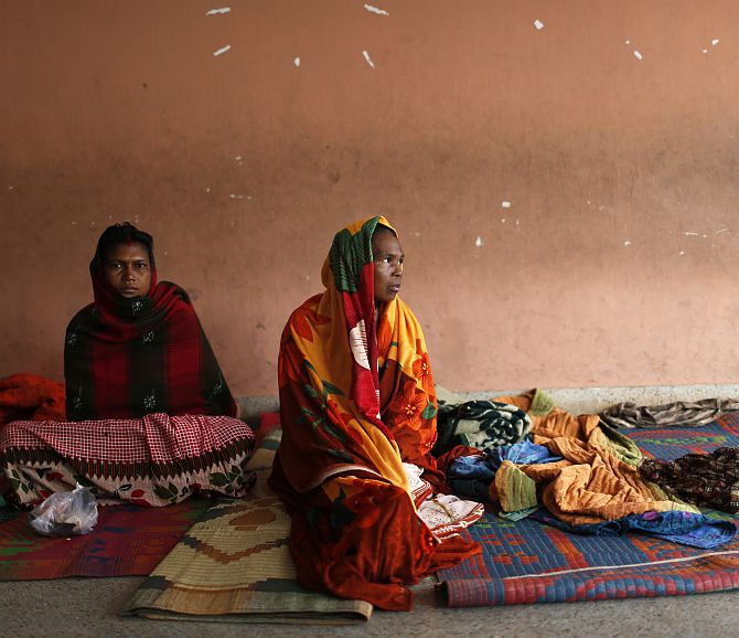 Women sit in a school compound after leaving their houses to take shelter from the impact of Cyclone Phailin
