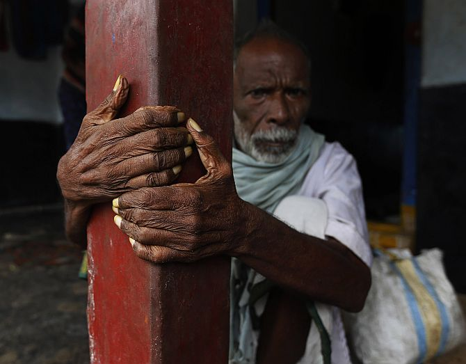A man sits outside his house as he waits to be evacuated to a safer place at Donkuru village in Srikakulam district