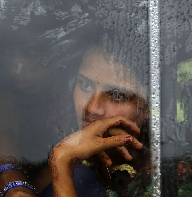A girl looks out from the window of a bus travelling towards a relief camp in Donkuru village in Srikakulam district