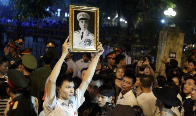 A man holds up a portrait of General Giap while gathering outside his home to pay homage in Hanoi.