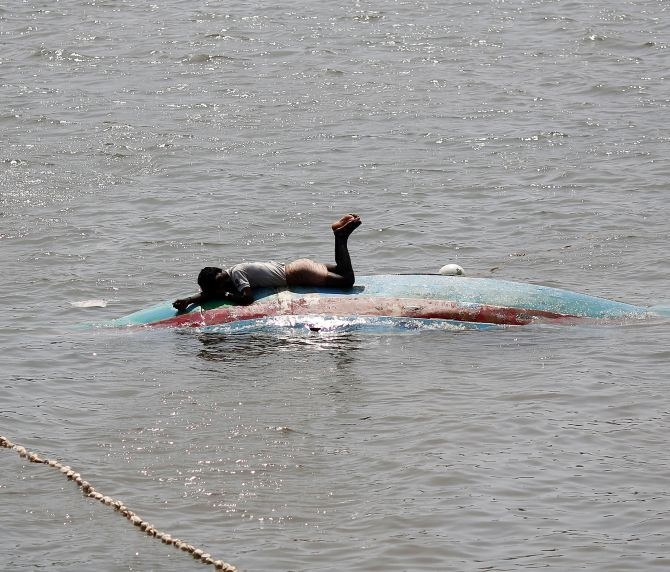 A fisherman lies on his overturned boat on Monday after Cyclone Phailin hit Gopalpur port in Odisha