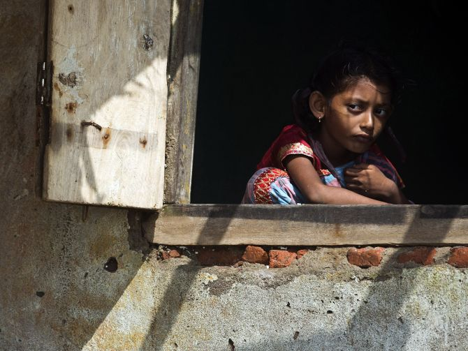 A girl looks out from the window of her partially damaged house on Monday after Cyclone Phailin hit Puri