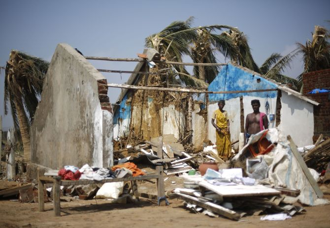 A couple stands inside their damaged house amid the debris after Cyclone Phailin hit Arjyapalli village in Ganjam district.