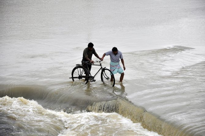Men cross a flooded road after heavy rains caused by Cyclone Phailin at Gaghra village in Jharkhand