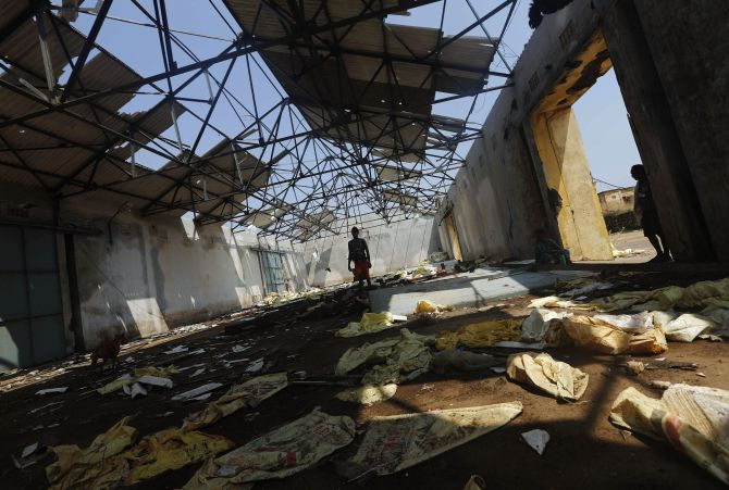 A fisherman walks inside a damaged port building on Monday after Cyclone Phailin hit Gopalpur village in Ganjam district.