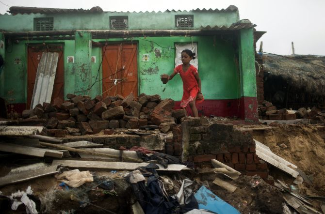 A girl removes debris from her damaged house on Monday after Cyclone Phailin hit Puri in Odisha