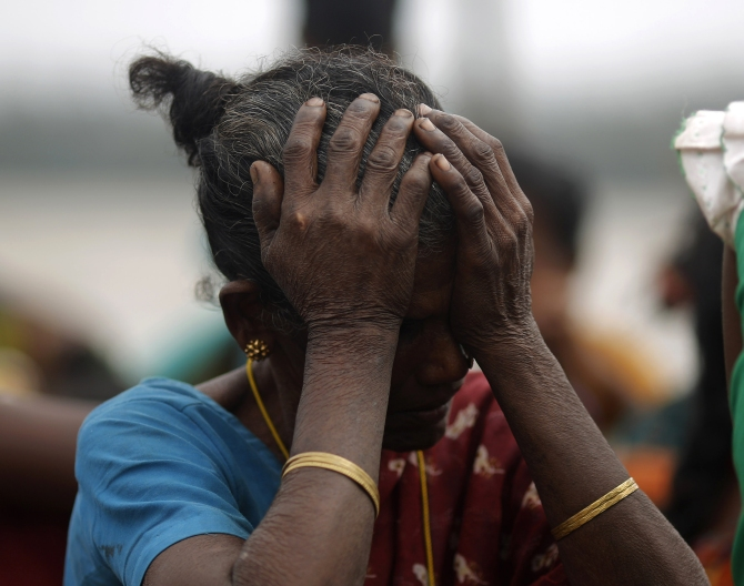 A woman holds her head after Cyclone Phailin hit Sunapur village in Ganjam district in Odisha