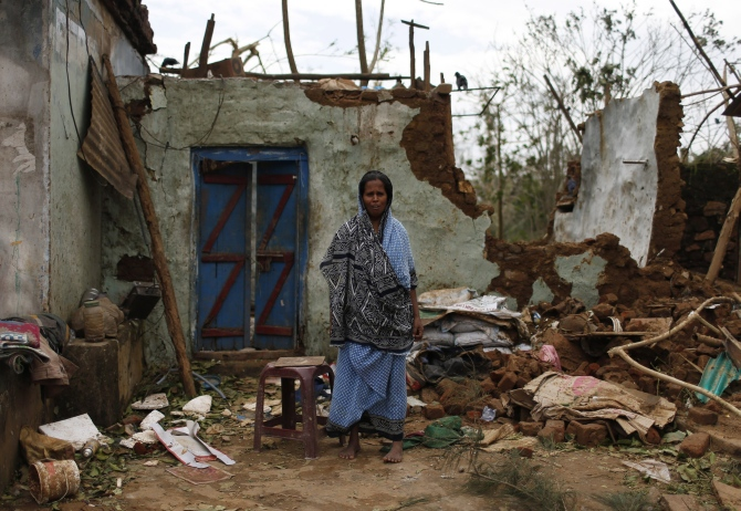 A woman stands outside her damaged house after Cyclone Phailin hit Gopalpur in Ganjam district in Odisha