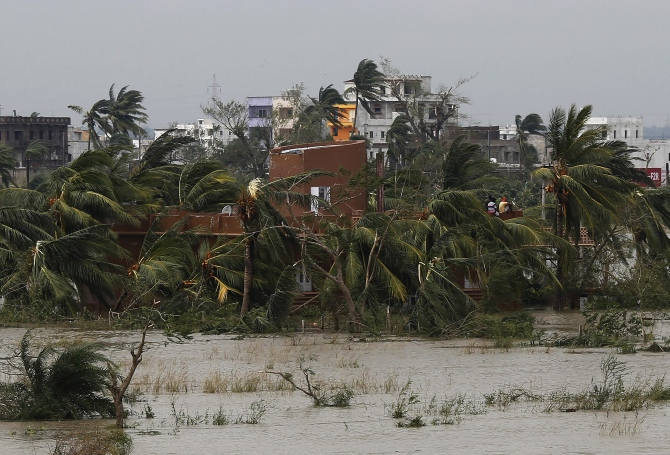People sit on the roof of a house after Cyclone Phailin hit Brahmapur town in Ganjam district in Odisha