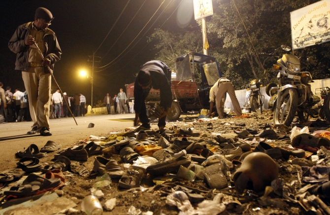 A man collects shoes left behind during a stampede last year in Junagadh district in Gujarat