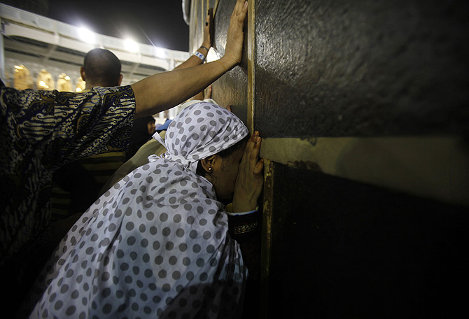 Muslim pilgrims touch the Kaaba at the Grand Mosque in the holy city of Mecca