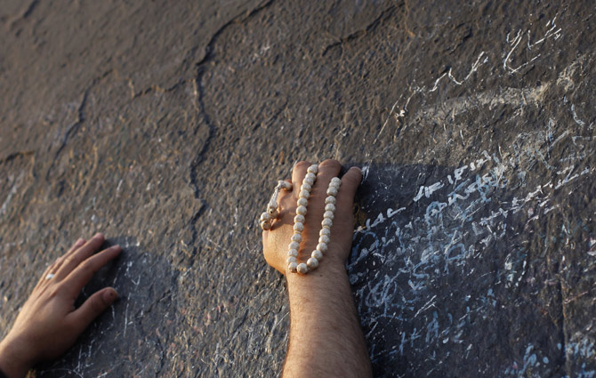 A Muslim pilgrim touches the rocks atop Mount Mercy on the plains of Arafat during the peak of the annual haj pilgrimage