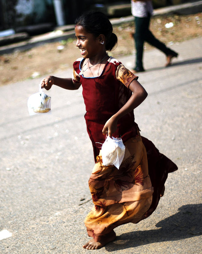 A girl runs home after receiving a free meal for breakfast at the cyclone-hit Gopalpur village, in Ganjam district in the eastern Indian state of Odisha