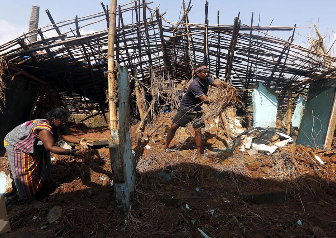 A fisherman and his wife clear the debris from their damaged house in Gopalpur