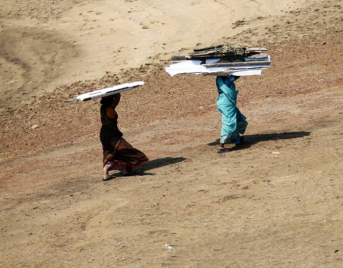 Women carry pieces of a temporary roof to rebuild their houses after Cyclone Phailin hit Arjyapalli village, in Ganjam district