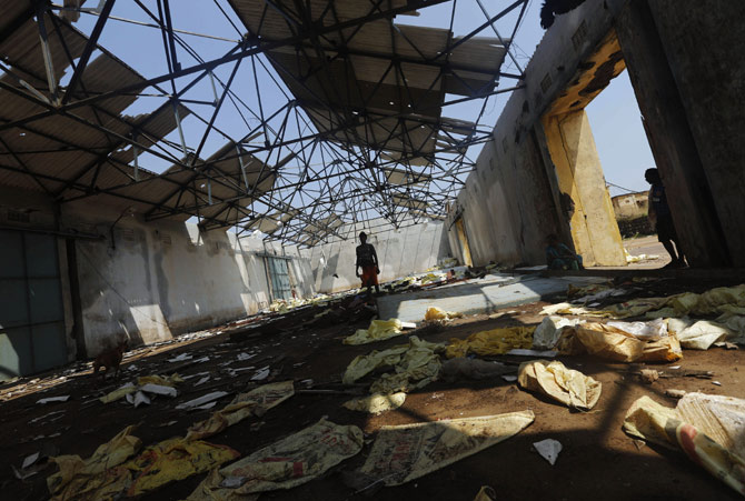 A fisherman walks inside a damaged port building in Gopalpur