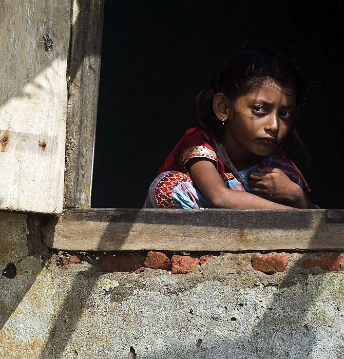 A girl looks out from the window of her partially damaged house