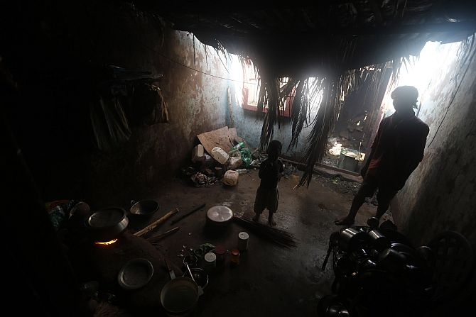 A man and his son stand inside their damaged house after Cyclone Phailin hit Gopalpur village in Ganjam district