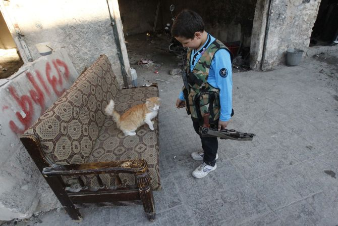 Abboud, 12, plays with a cat while holding his weapon in Aleppo's Sheikh Saeed neighbourhood