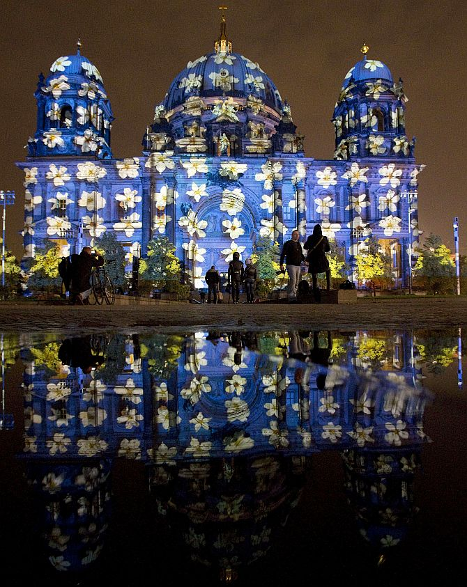 People look at a light installation at the Berlin Cathedral during the opening day of the Festival of Light show in Berlin