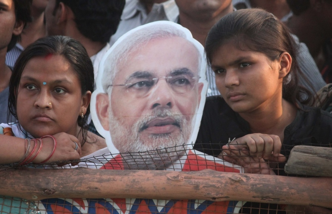 Modi supporters pose with a cutout of the Gujarat chief minister