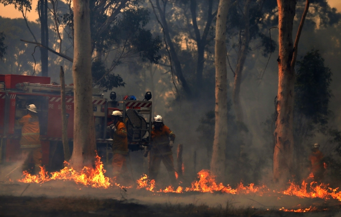 Firefighters work at the scene of a bushfire in Casltereagh, near Sydney