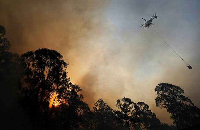 A helicopter carries water to be dropped on a bushfire in Castlereagh, near Sydney