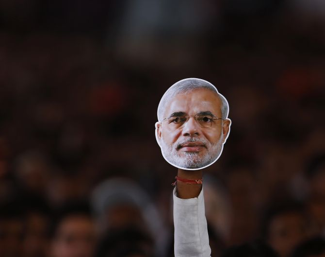 A supporter of BJP holds a mask of Narendra Modi during a campaign rally