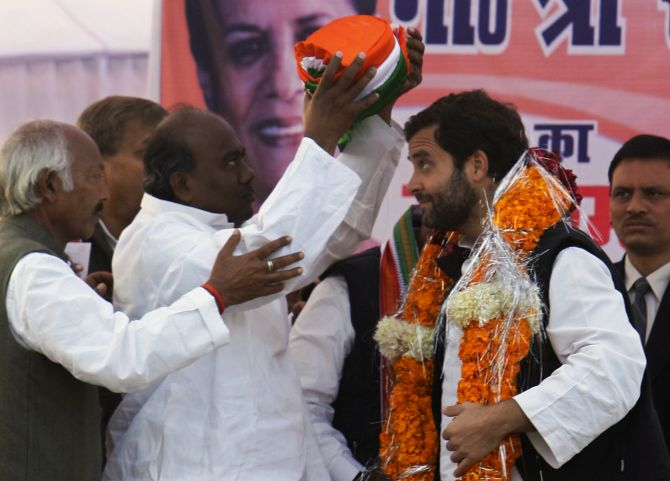 Rahul Gandhi is presented a turban by his party workers during an election campaign rally in UP