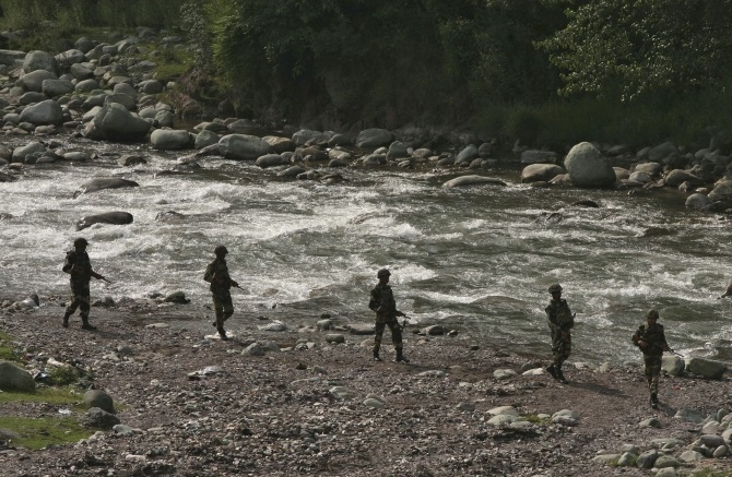 Border Security Force soldiers patrol next to a stream near the Line of Control in Poonch