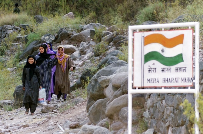Kashmiri border village girls walk near a signboard that reads. 'My India (is) Great' at Odusaa, 127 kms west of Srinagar