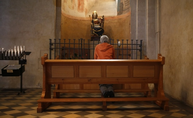 A woman kneels in prayer inside Limburg cathedral