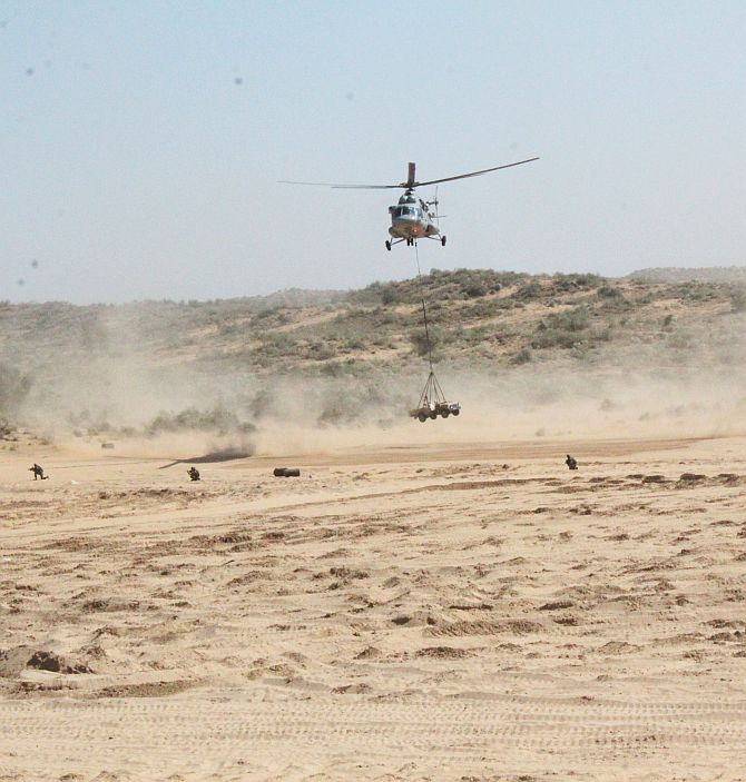 An Indian Army helicopter inserts a team vehicle during a drill
