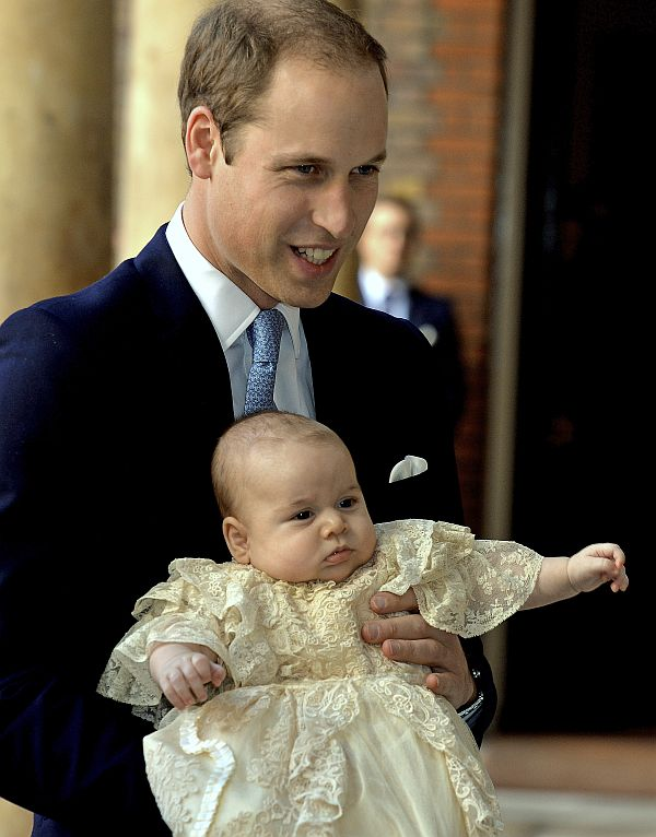 Britain's Prince William carries his son Prince George as they arrive for his son's christening
