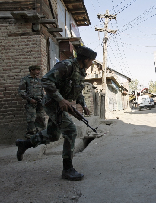A soldier runs during a gun battle with suspected terrorists in Sopore, 48km north of Srinagar.