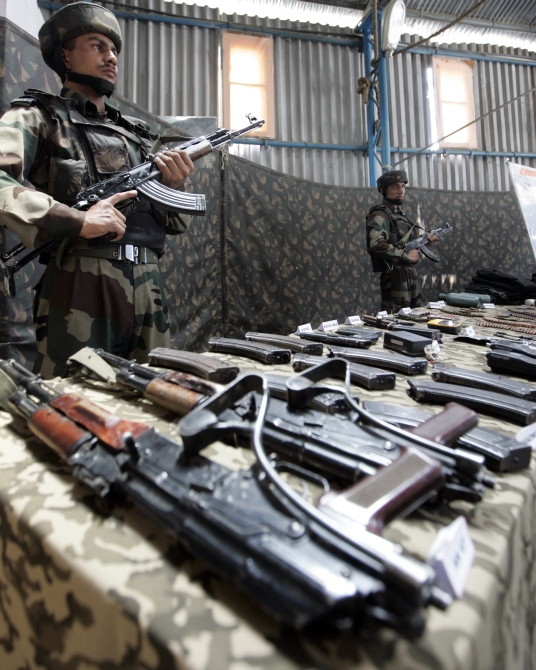 Army soldiers stand guard near seized arms and ammunitions during a news conference at an Indian army garrison in Kupwara, 90 km north of Srinagar