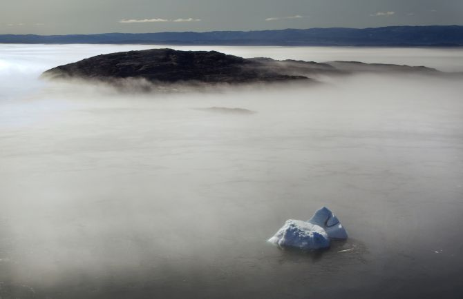 A large iceberg is seen on the edge of a morning fog over Frobisher Bay, Nunavut in the Canadian Arctic