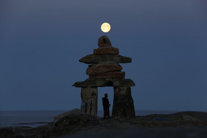A man looks at a giant inukshuk as the moon rises above it in Rankin Inlet, Nunavut