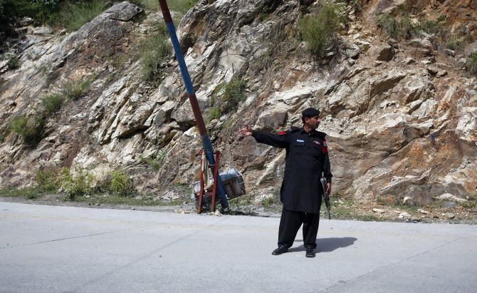 A police officer guards a check post on the outskirts of Gilgit